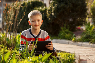 Happy boy outdoors using his tablet computer for  playing