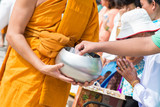 give alms to a Buddhist monk in Songkran Festival
