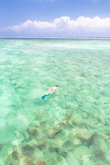 woman snorkeling in turquoise blue sea.