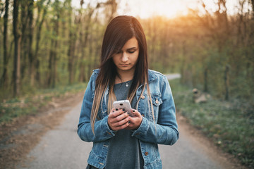Young brunette girl messaging smartphone on the park