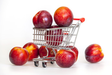 Large red plums in the store cart
