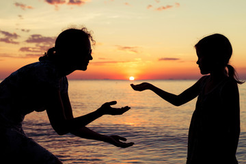 Mother and daughter playing on the beach at the sunset time.