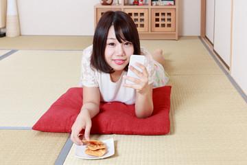 せんべいを食べながらスマホを使う女性