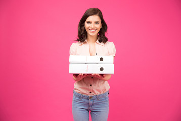 Smiling young woman standing with folders
