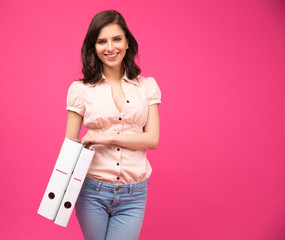 Smiling young woman holding folders