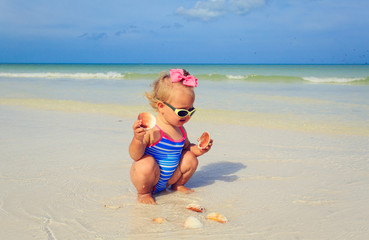 cute little girl playing with shells on the beach