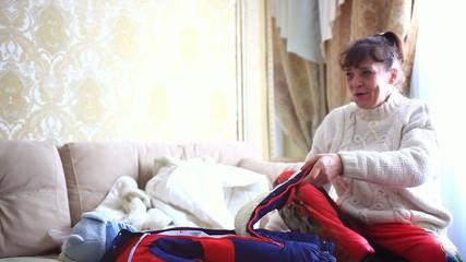 Happy grandmother undresses her grandson