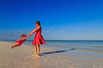 mother and daugher playing on summer beach