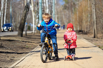 little boy and toddler girl riding bicycle, scooter outdoors