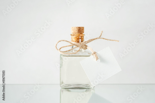 Bottle with transparent liquid on the light background - 81671383