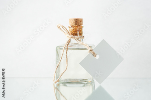 Bottle with transparent liquid and empty label on the light back