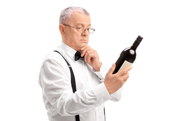 Elegant senior reading the label on bottle of wine