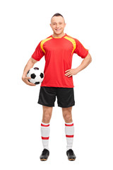 Full length portrait of a young soccer player holding a ball