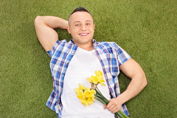 Handsome man lying on grass and holding flowers