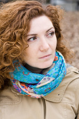 Portrait of a young beautiful redheaded girl in a bright scarf