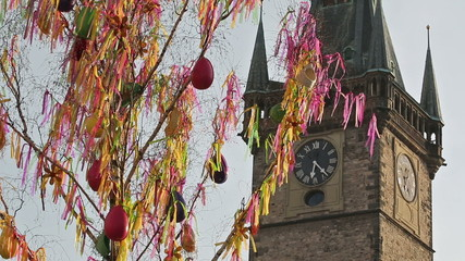 Old clock tower behind the waving Easter fringes
