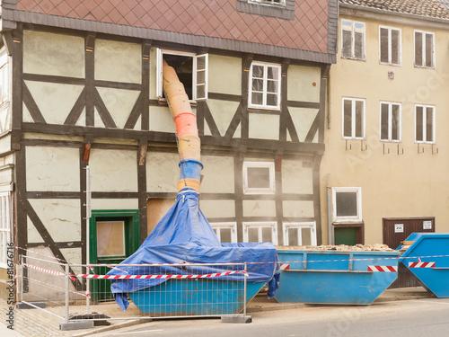 Leinwanddruck Bild Staubige Fachwerkhaus-Sanierung mit einer Schuttrutsche