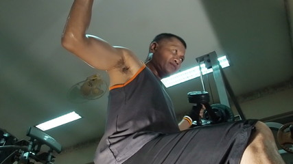 Strong man lifting hand weights in the gym. Slow motion.