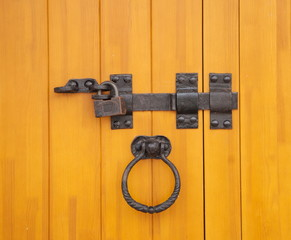 Wooden door with old forged bolt and lock