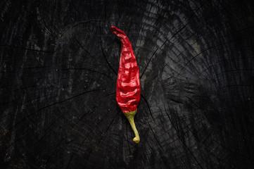 Hot red pepper lies on a dark board