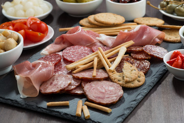 Assorted meat snacks, sausages and pickles on a blackboard