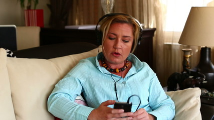 woman sitting sofa and listening music with smartphone