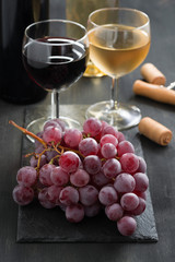 bunch of red grapes and wine glasses on a dark background