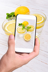 Hands taking photo lemon drink with smartphone.