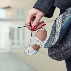Женская рука держит солнцезащитные очки.