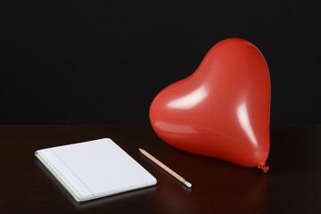 Globo rojo y cuaderno