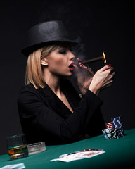 Beautiful young woman smokes a cigar during a poker game