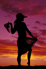 silhouette of a woman in a skirt out hat and sandles in hand