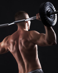 Man with bare chest lift weights on black background.