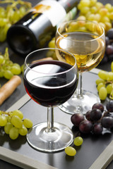 red and white wine in glasses, fresh grapes in the background