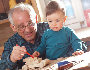 Senior carpenter and his grandson working in the workshop