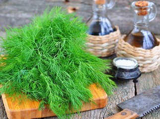 Bunch of fresh dill with olive oil on a wooden table