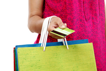Female hand holding shopping bags and credit card on white backg