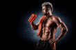 Young adult man drinking protein shake in gym. Black background.