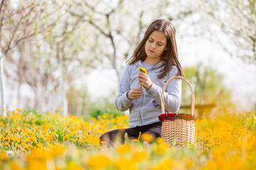 Child outdoors with dandelions. Girl sitting on a meadow