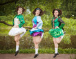 Three young beautiful girls in irish dance dress and wig dancing