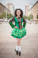 Young woman in irish dance dress and wig posing