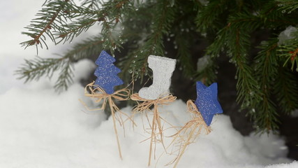 Beautiful wooden toys under the fir tree in snow in winter