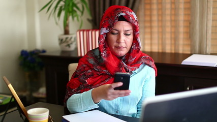 Muslim Business Woman Working with Laptop and Talking Phone