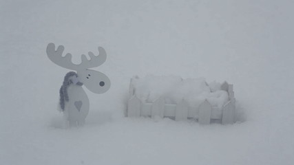 Decorative white wooden fence and elk in the snow in the winter