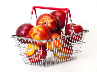 Large red plums in a metal basket for purchases