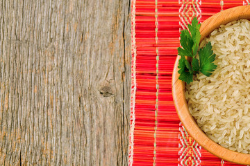 Isolated bowl with brown uncooked rice and leaf of parsley
