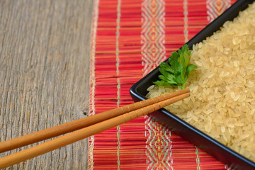 Plate with brown uncooked rice and leaf of parsley