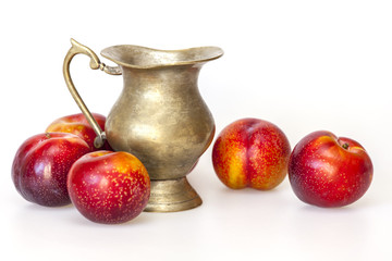 Large red plums and metal jug for juice