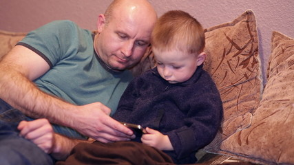 Little boy with his uncle watching a movie on your phone