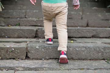 石の階段を登る子供の足
